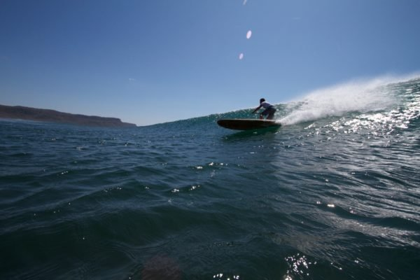 Harris surfing his otter wooden paddleboard