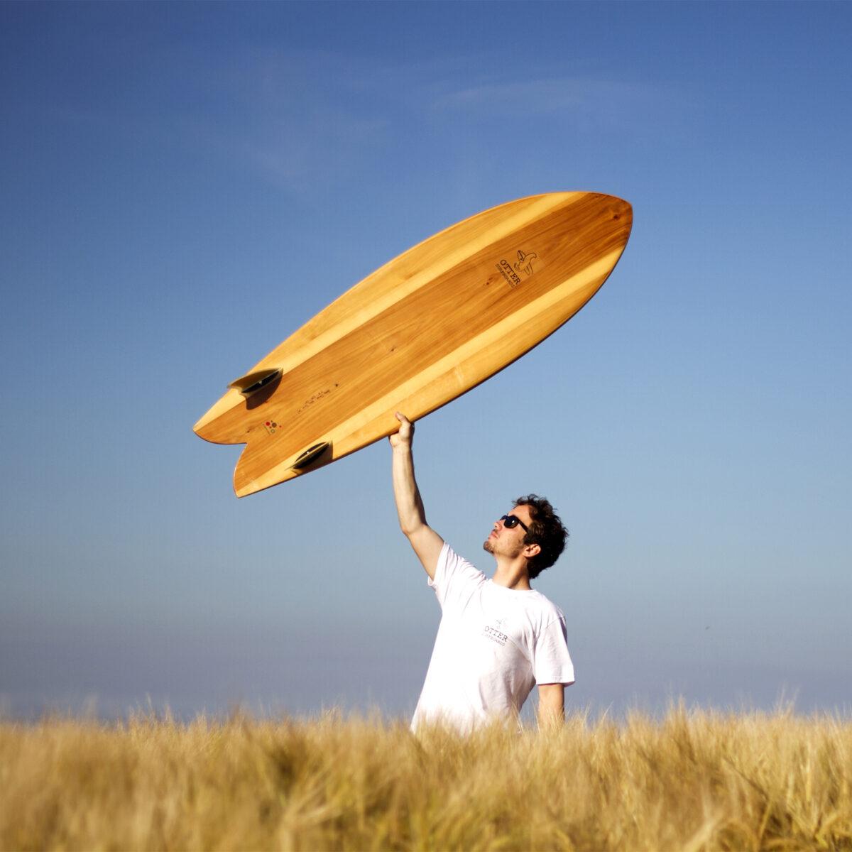 otter wooden surfboard fetch fish held aloft corn field