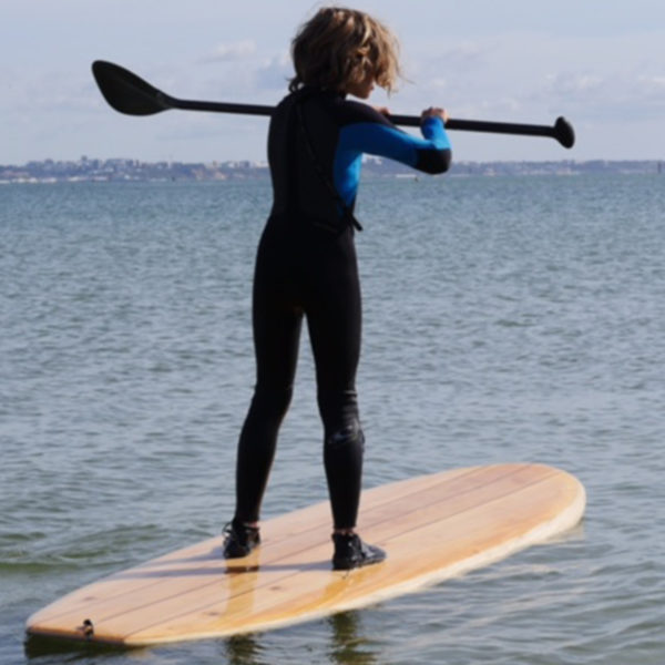 Otter surfboards wooden stand up paddle board on the water with boy
