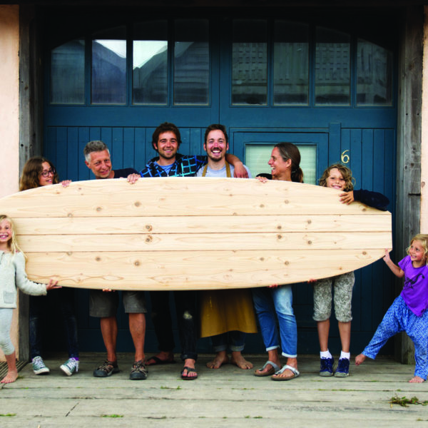Family with wooden paddleboard outside the otter surfboards workshop with Chris and James