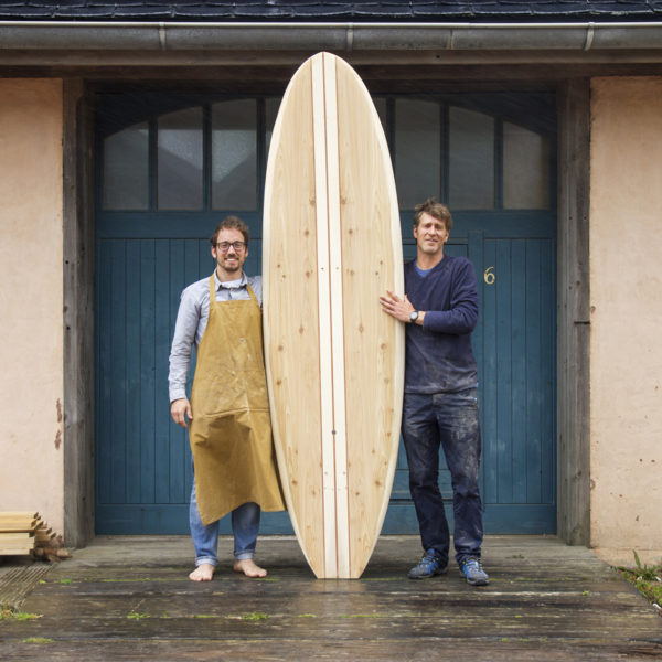 David and James Otter outside the blue workshop doors with an Otter surfboards wooden paddle board