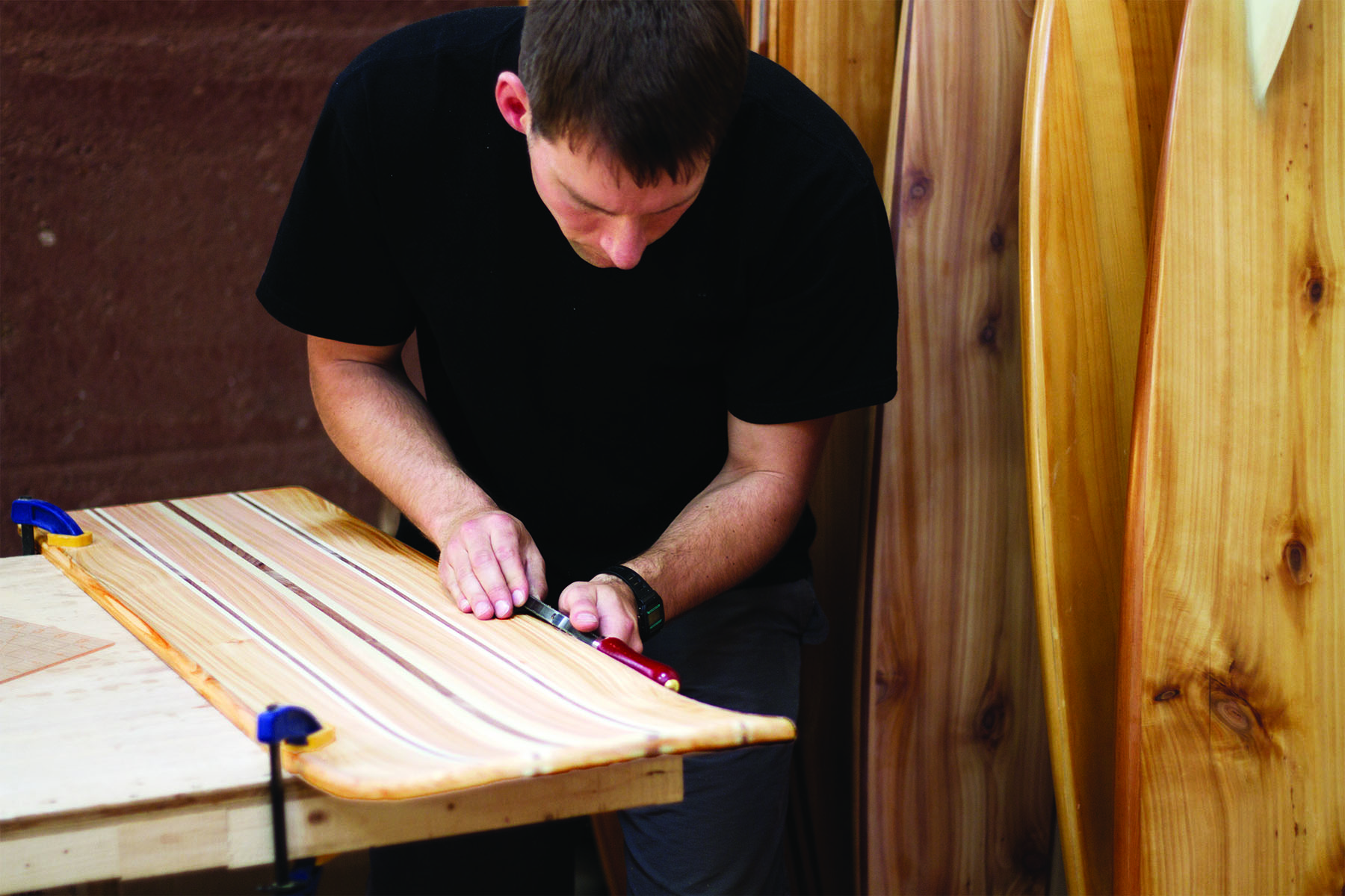 Rasping the rails of an otter surfboards wooden bellyboard workshop course Tony