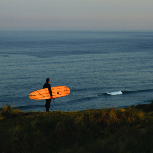 James Otter Seasaw at Perran Sands Wooden Surfboard with surfer on the coast in Cornwall