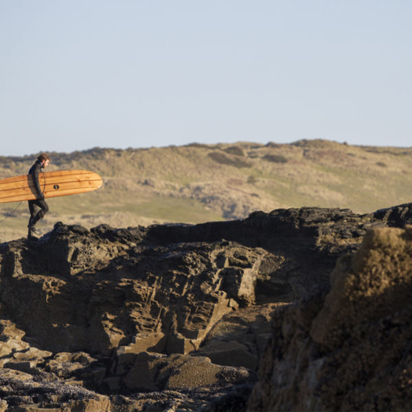 Chris walks back up the cliff with the Otter Surfboards wooden longboard Seasaw at Godrevy