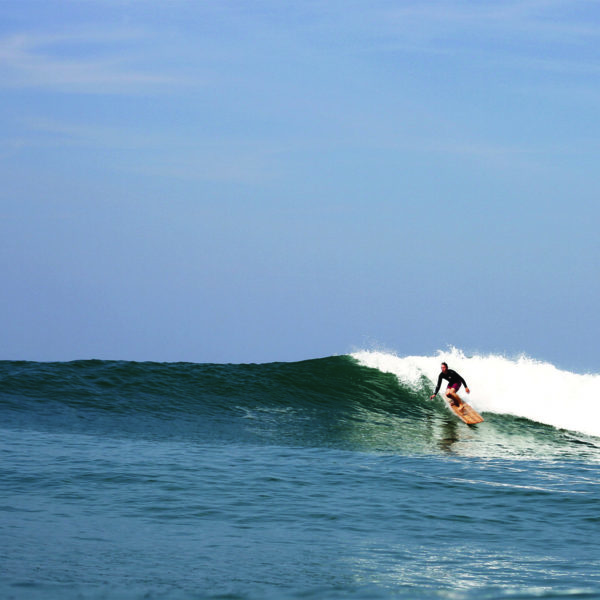 James Otter drops into a wave on the Pier wooden surfboard at Chapel Porth, Cornwall in summer. Riz Boardshorts