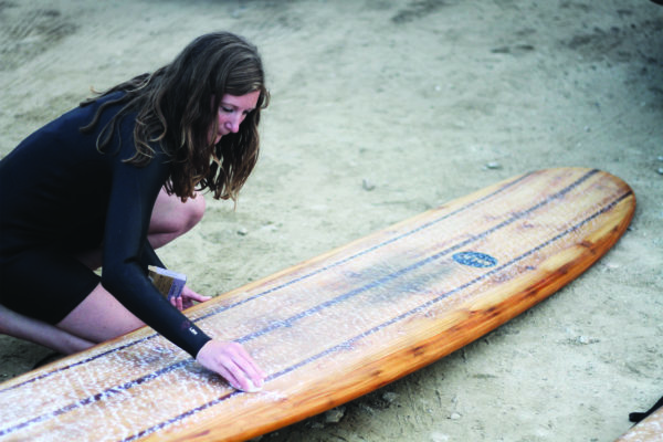 Rebecca Pepperell waxing the Otter Surfboards Seasaw wooden longboard at Perranporth in Cornwall