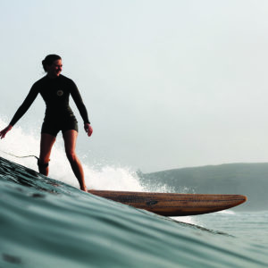 Rebecca Pepperell Surfing the Otter Surfboards Seasaw wooden longboard at Perranporth in Cornwall