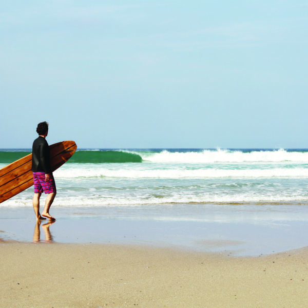 James Otter with the Pier wooden surfboard at Chape Porth, Cornwall in summer.