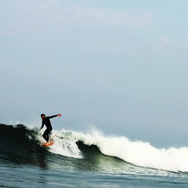 Chris Brunt hangs five noseride on a Seasaw Wooden Otter Surfboard in surf