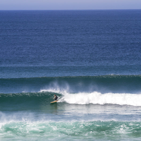 James Otter classic lines at Gwithian in the summer on his wooden surfboard Wicket in St Ives Bay