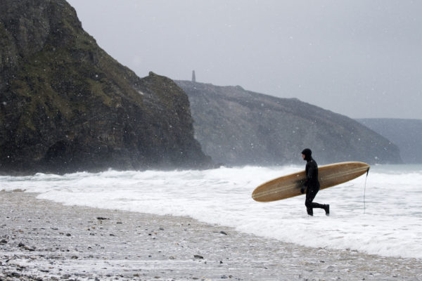 Otter Wooden Surfboard being carried out of the surf at Porthtowan in the snow. Wicket