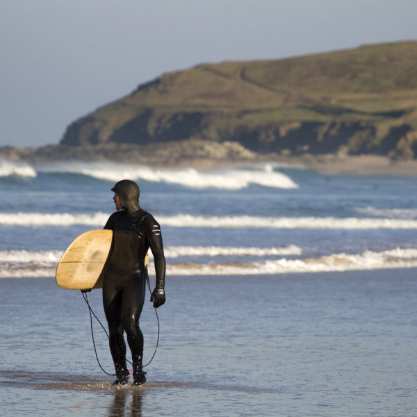 James Otter looks back on a few waves with his wooden surfboard Coaster under his Arm in his Finisterre wetsuit.