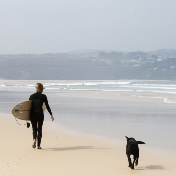 Sophie Hellyer walks along a sandy beach in the wind at st Ives bay with buddy the dog and her otter surfboards wooden surfboard Coaster