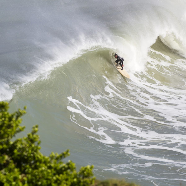 Matt Smith takes cover on an Otter wooden surfboard coaster at St Agnes, Cornwall