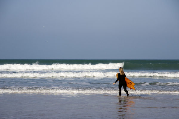 Sarah walks into the surf with the otter surfboards wood burner Wooden surfboard at Gwithian, Cornwall shot from the beach