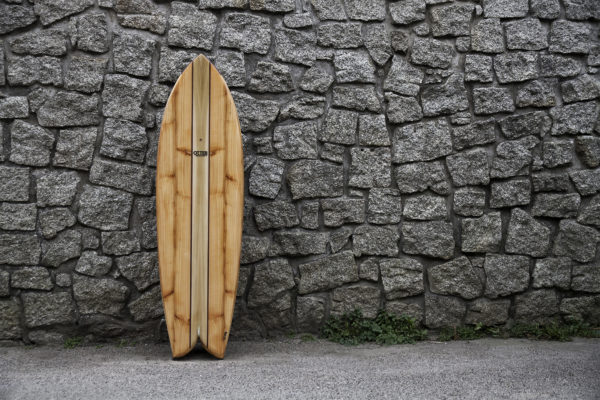 biff lancaster wooden otter surfboard woodburner fish against a stone wall