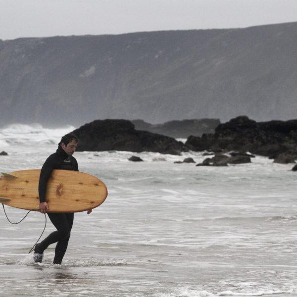 Seadar James Otter Surfing wooden surfboard at Porthtowan walking out