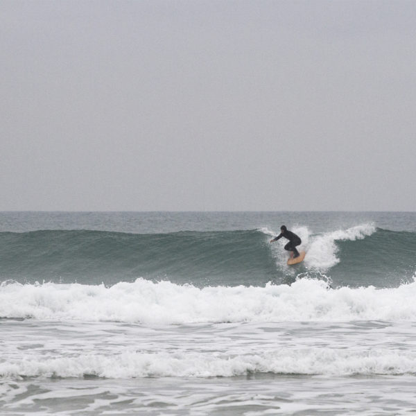 Seadar James Otter Surfing wooden surfboard at Porthtowan dropping in