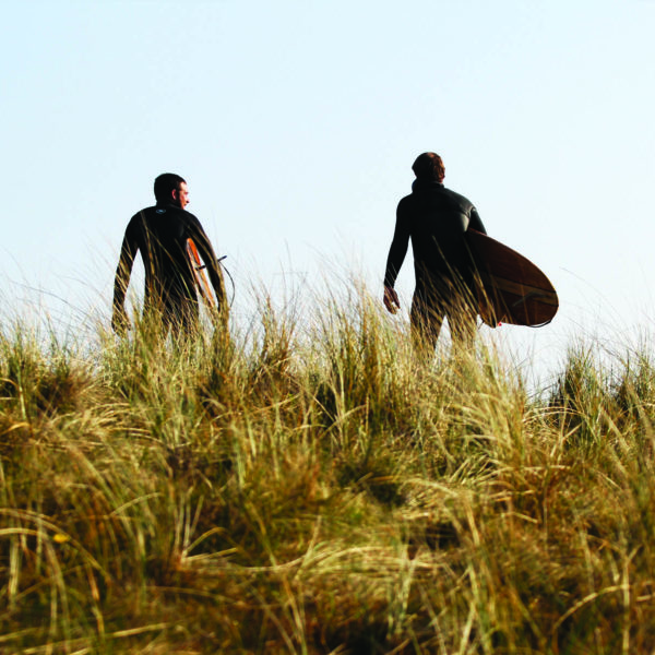 Chris and Gideon walk along the sand dunes in maram grass with Otter Surfboards wooden Island Hopper and Jetty at Gwithian