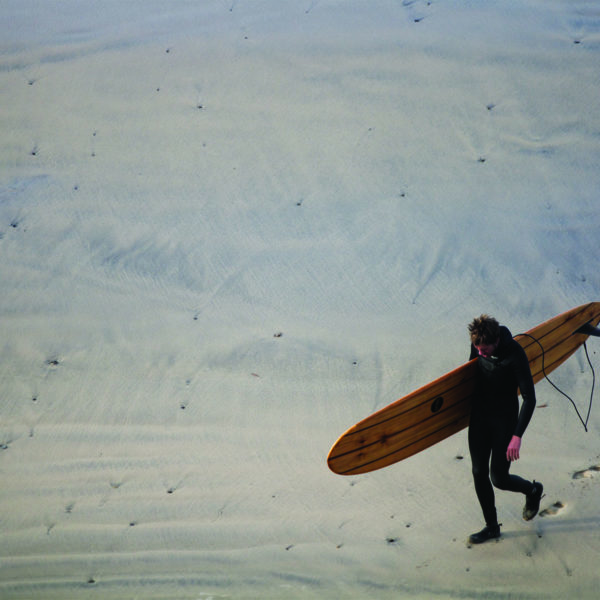 Mat Arney walks back across the sand at Gwithian with his wooden Otter Surfboards Pier.