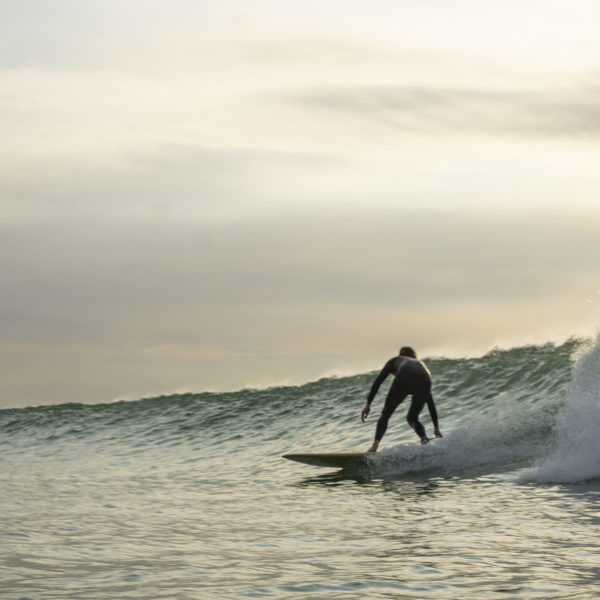 Lawrence Stafford drawn out bottom turn blur on an Otter Wooden Coaster Surfboard at Gwithian in Cornwall
