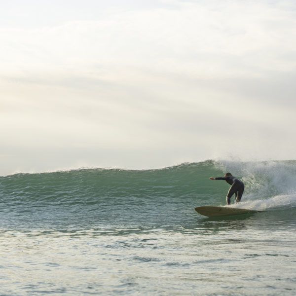 Lawrence Stafford bottom turning on an Otter Wooden Coaster Surfboard at Gwithian in Cornwall