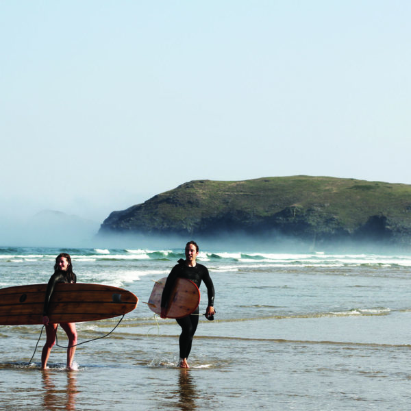 James Otter and Becky exit the surf at Perranporth, Cornwall with their wooden surfboards. Seasaw and Seadar