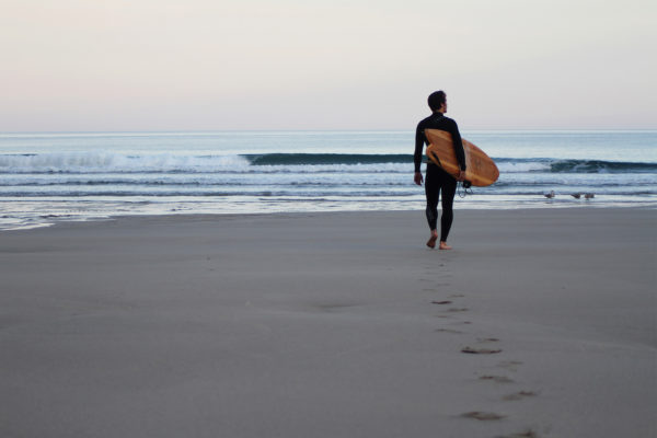 James Otter walking out to the surf at Chapel Porth, Cornwall with his fetch wooden surfboard.