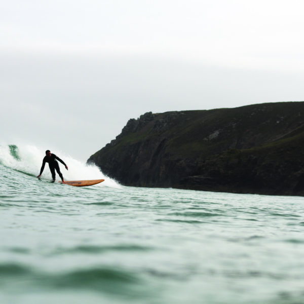 Chris bottom turning the Pier and Chapel Porth, Cornwall. Otter wooden surfboard