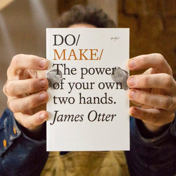 James Otter holding his book Do Make in the Otter Surfboards Workshop